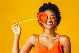 Portrait of a happy young woman holding orange Gerbera daisy covering her eye with eyes closed