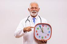 Portrait Of Senior Doctor Holding Clock On Gray Background.