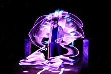 Portrait Of A Boy Standing With A Baseball Bat. Night Scene At Lightpainting. Abstract Shape With A Bright Purple Saber In Long Exposure Mode.