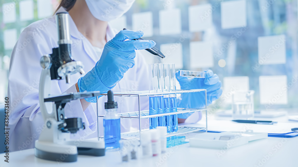 Fototapeta Medical or scientific researcher or man doctor looking at a test tube of clear solution in a laboratory