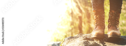 Fototapeta Female legs shod in Hiking boots on the forest background