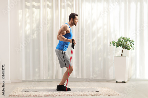 Carta da parati Man exercising with a resistance band at home