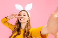 Woman In Easter Bunny Ears, Takes A Selfie On Her Phone And Shows The Gesture Of Peace, On An Isolated Pink Background