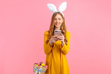 Woman In The Ears Of An Easter Bunny, Holding A Basket Of Easter Eggs, With A Mobile Phone In Her Hands On An Pink Background