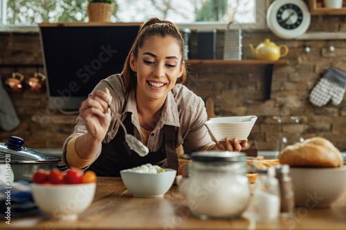 Photo Smiling woman enjoying in preparing food in the kitchen.