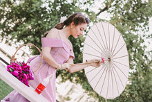 Portrait Of Stylish Beautiful Romantic Girl In Vintage Dress And Pin Up Hairstyle Opening Umbrella In Hands. Attractive Young Tender Retro Woman Sitting At Table In Park. Picnic On Summer Garden