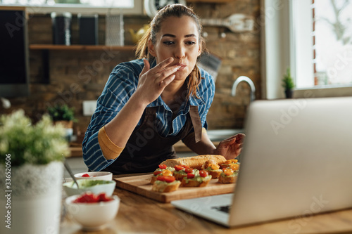 Obraz Young happy woman using laptop while preparing bruschetta in the kitchen. - fototapety do salonu