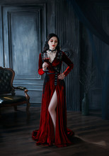 Medieval Young Woman Vampire Holds Glass Of Bloody Wine In Hand. Red Long Sexy Dress Train. Gothic Dark Quuen Lady. Black Long Wavy Hair Sexy Naked Leg. Backdrop Vintage Night Room Interior. Halloween
