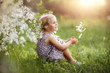 baby girl walks in spring in a blooming garden, happy childhood, cherry blossoms, month of may