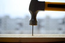 A Powerful Hammer Hammers A Nail Into A Wooden Board.