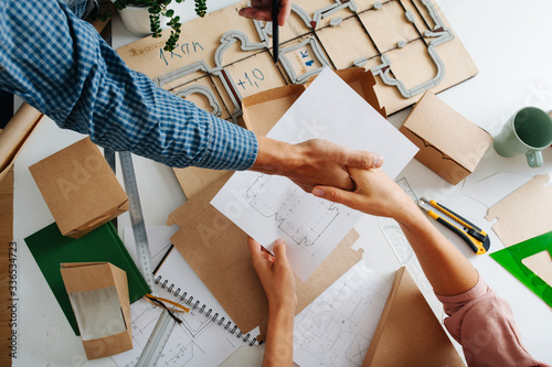 Box craftsman and manufacturer working out schematics of a box, striking a deal Canvas Print