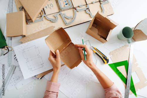 Fotografie, Obraz Box maker analysing box, prepared to make marks with a pencil