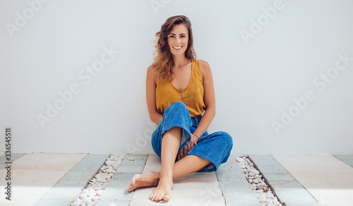 Leinwand Poster Woman sitting on terrace floor and looking at camera