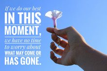 Inspirational Quote - If We Do Our Best In This Moment, We Have No Time To Worry About What May Come Or Has Gone. With Hand Holding Water Spinach Flower Against Blue Sky Background In Low Angle View.