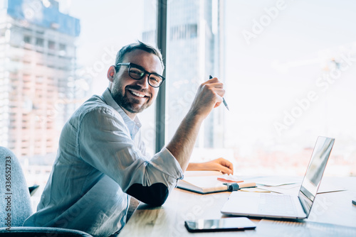 Photo Portrait of cheerful male entrepreneur in classic eyewear smiling at camera whil