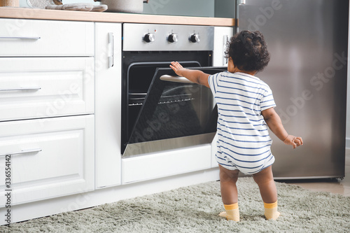 Obraz Little African-American baby near stove in kitchen. Child in danger - fototapety do salonu