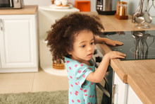 Little African-American Girl Playing With Stove In Kitchen. Child In Danger
