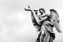 Low Angle View Of Angel Statue With Cross Against Clear Sky