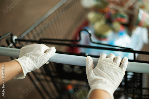 Photo Woman wearing gloves to prevent coronavirus while using a shopping cart