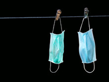 Disposable Medical Mask Hanging On Pegged Clothesline For Reused,Concept Of Fight Against Coronavirus From WHO: COVID-19.