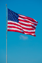 US American Flag Waving In Wind. Blue Sky On Background. Star Striped Patriotic Symbol. United States Of America. 4th Of July Independence Day.