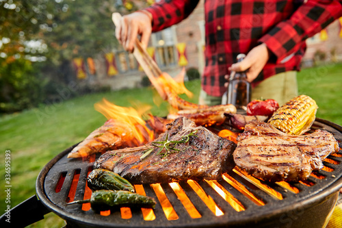 Man holding a beer grilling meat on a BBQ Canvas