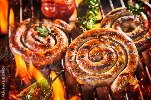 Close up on spicy coils of sausage grilling on BBQ Fototapeta