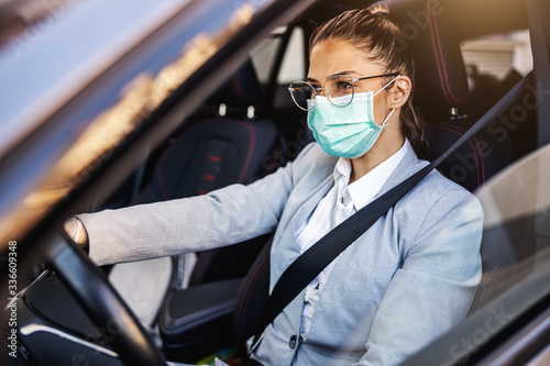 Obraz na plátně Young woman with protective mask and gloves driving a car