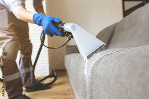 Close up man hand in protective rubber glove cleaning sofa with professionally extraction method Slika na platnu