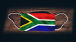 canvas print picture - South Africa National Flag at medical, surgical, protection mask on black wooden background. Coronavirus Covid–19, Prevent infection, illness or flu. State of Emergency, Lockdown
