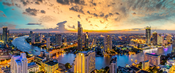Aerial view Bangkok City skyline and skyscraper on Sathorn Road business and financial in Bangkok downtown, Panorama of Taksin Bridge over Chao Phraya River, Bangkok, Thailand at sunset.