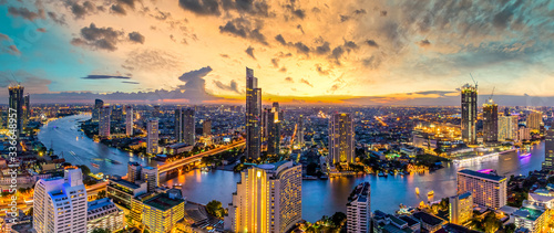 Canvas Print Aerial view Bangkok City skyline and skyscraper on Sathorn Road business and financial in Bangkok downtown, Panorama of Taksin Bridge over Chao Phraya River, Bangkok, Thailand at sunset