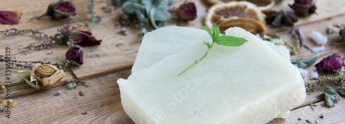 Fotografia Handmade soap bars with herbs on  wooden table, soft focus,banner