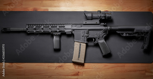 AR-15 rifle on wooden table. Wallpaper Mural