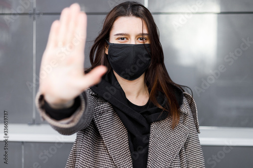 Fototapeta Young woman wearing face mask. Handsome woman in black hoodie wear black medical mask. Pandemic coronavirus covid-19 quarantine period concept. obraz