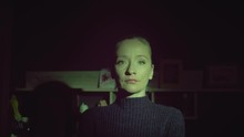 A Young Blond Woman With A Calm Gaze Stands In The Darkness Lit By Green Light. She Looks At The Camera. The Camera Approaches Her. Dolly Shot.