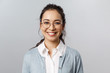 Close-up portrait of attractive, friendly-looking asian female office worker, employee or teacher in glasses, smiling broadly camera with enthusiastic attitude, stand grey background