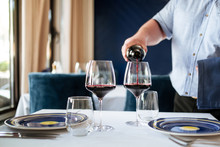 Male's Hand Pouring Dry Red Wine In Glasses On The White Table In Restaurant, Horizontal, Side View