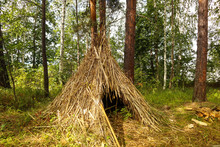 Simple Shelter Of Dry Grass In The Forest. Survival Hut Or Primitive House In Wild Nature. Natural Sample Of Construction Is Shown On A Sunny Summer Day.