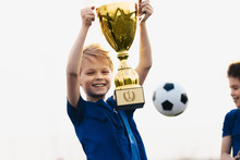 Happy Boy Rising Golden Trophy. Child Winning Sports Competition. Overjoyed Kid Holding Golden Prize Award. Soccer Ball In The Background