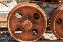 Close-up Of Rusty Wheels Of An Ancient Mining Cart On The Rails. Friuli Venezia Giulia, Italy, Europe