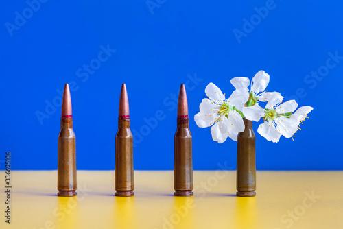 Gun cartridges on blue yellow background close up Wallpaper Mural