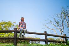 公園の柵に座って遠くを見る女の子