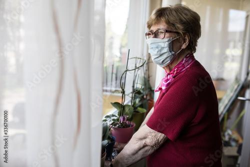 Photo Seniorin mit Mundschutz schaut aus dem Fenster