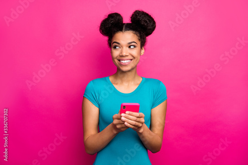 Fototapeta Photo of funny youngster dark skin lady two buns hold telephone hands look side empty space interested wear blue casual t-shirt isolated magenta color background obraz