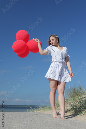 Obraz na plátně young happy girl in dress with red balloons