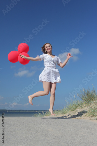 Fototapeta young happy girl in dress with red balloons