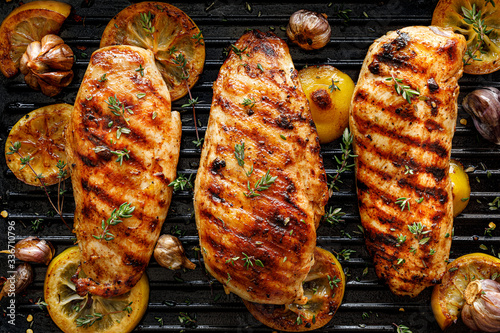 Carta da parati Grilled chicken breasts with thyme, garlic and lemon slices on a grill pan, top