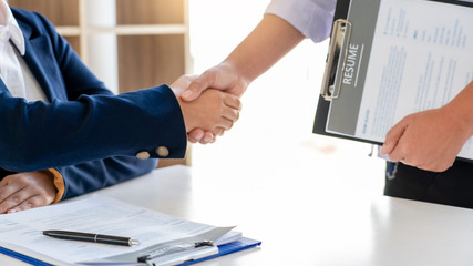 Cheerful interviewer hr manager welcoming women applicant at job interview handshaking at group meeting talk and effective negotiation