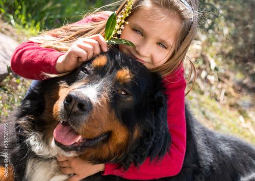 Fotografia La petite fille blonde embrasse son gros chien bouvier bernois
